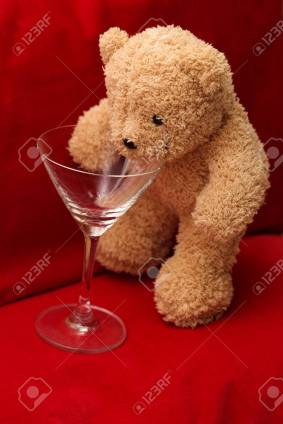 Brown teddy bear holds wine glass on red background
